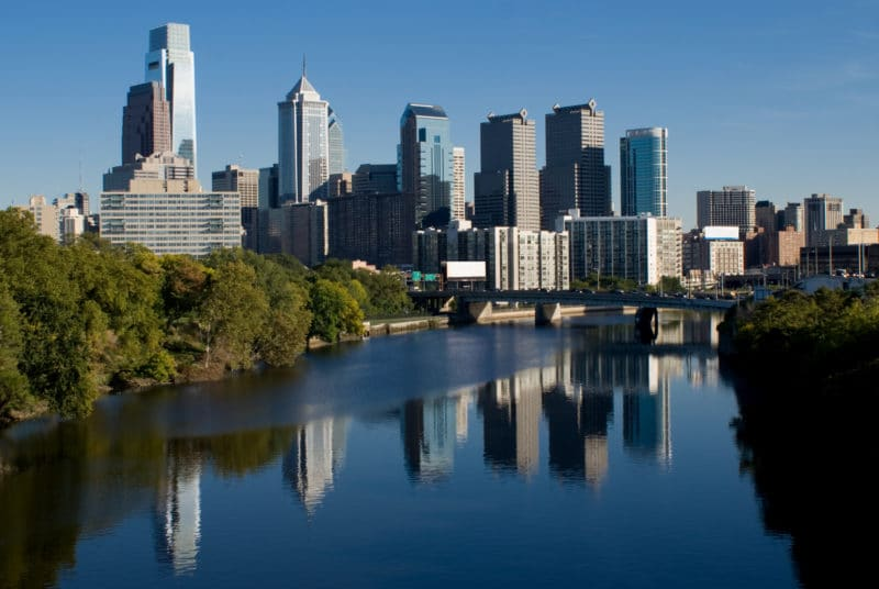 The skyline of Philidelphia. The Schuylkill river is in the foreground. The tallest buildings are on the left side. The buildings are reflected in the surface of the river.