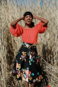 Bold orange blouse hands up smiling